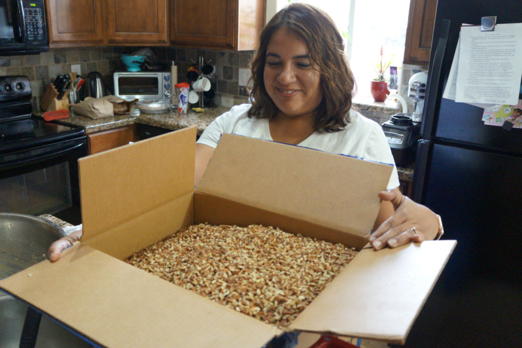 Sarah Dunlop opens a box of pecans to go into her ungranola
