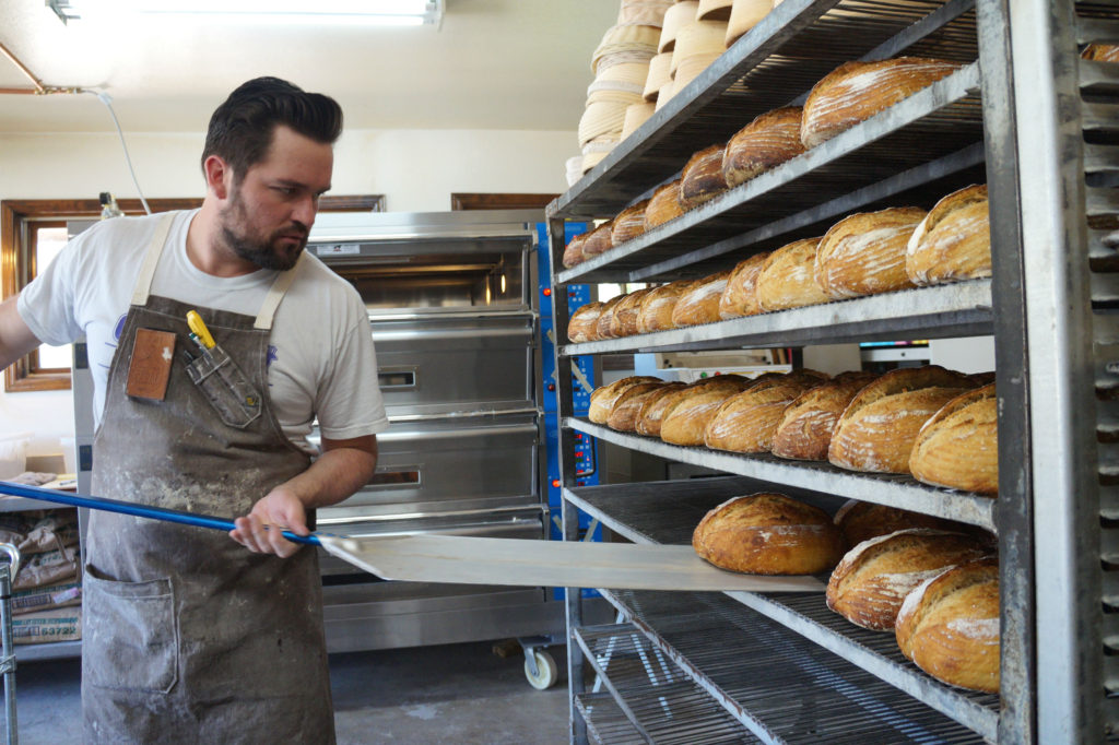 Jon moves baked loaves of sourdough from the oven to cooling racks