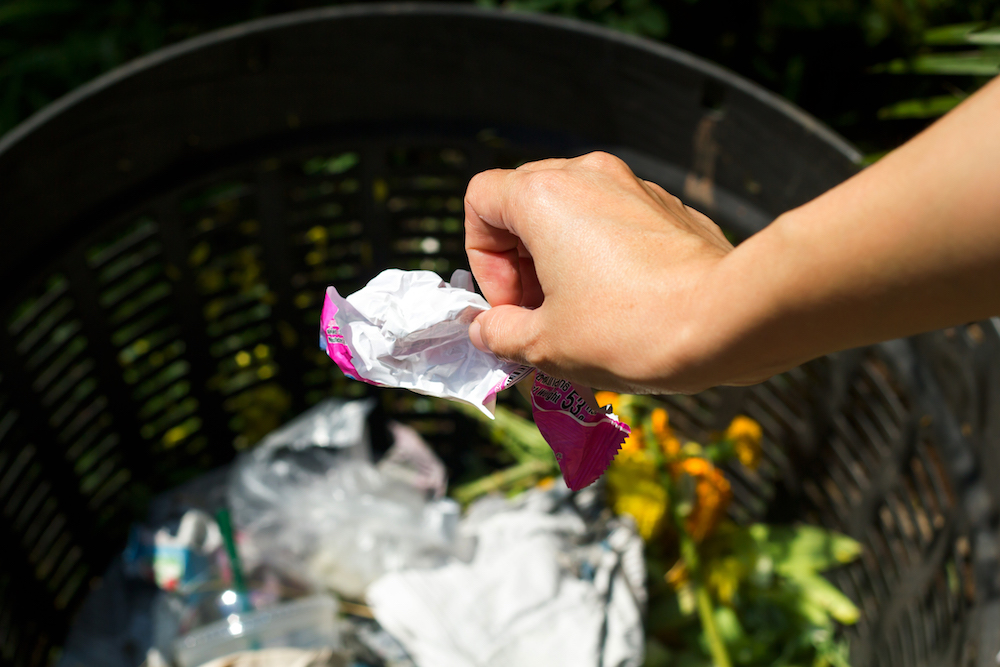 Closeup cropped portrait of someone tossing crumpled piece of ice-cream plastic package in trash can, isolated outdoors green trees background
